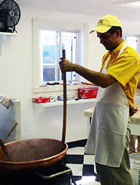 """J-1 SWT participant Danilo Babic (Serbia) makes fudge in front of visitors dubbed """"fudgies"""" by the Mackinac locals."""
