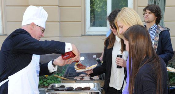 Ambassador Theodore Sedgwick prepares hamburgers for SWT alumni and prospective participants in May.