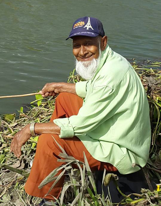 Man sits in front of river holding fishing stick