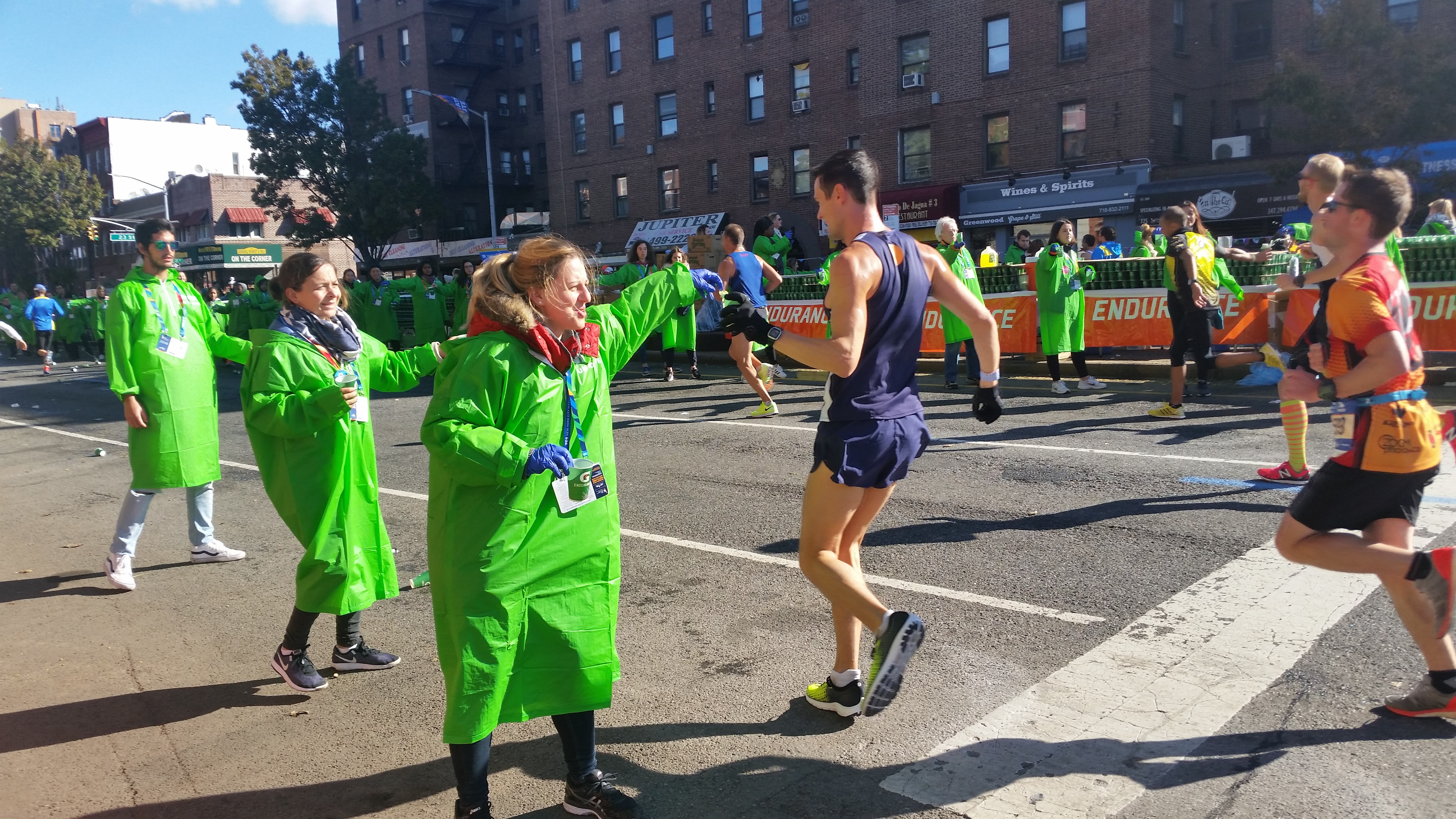 Three young volunteers in green parkas hold out cups to passing marathon runners