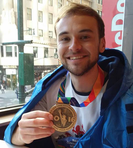 Liam Godbert Brown shows off his NYC Marathon Finisher Medal.