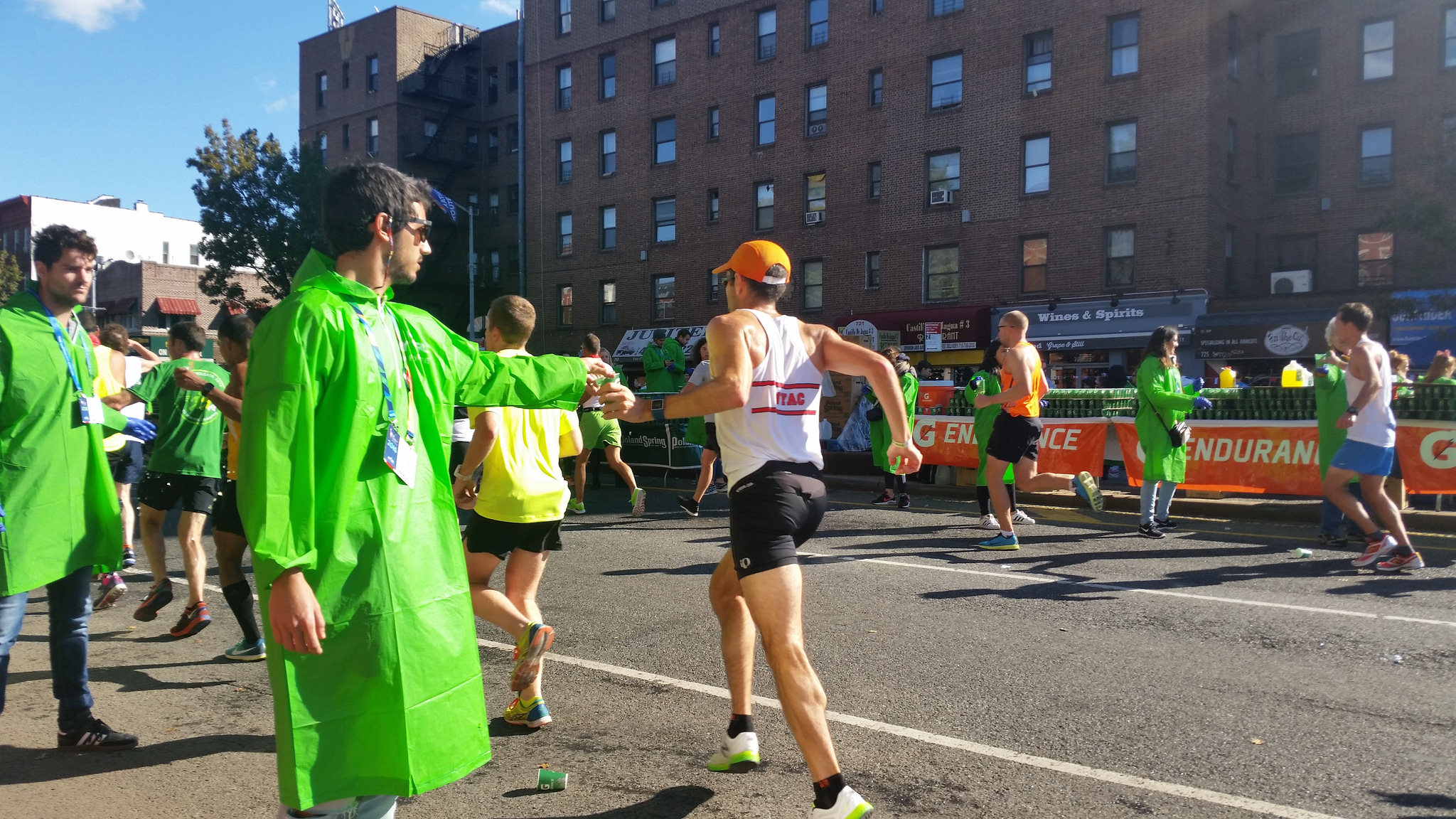 Young man hands water to passing marathon runner