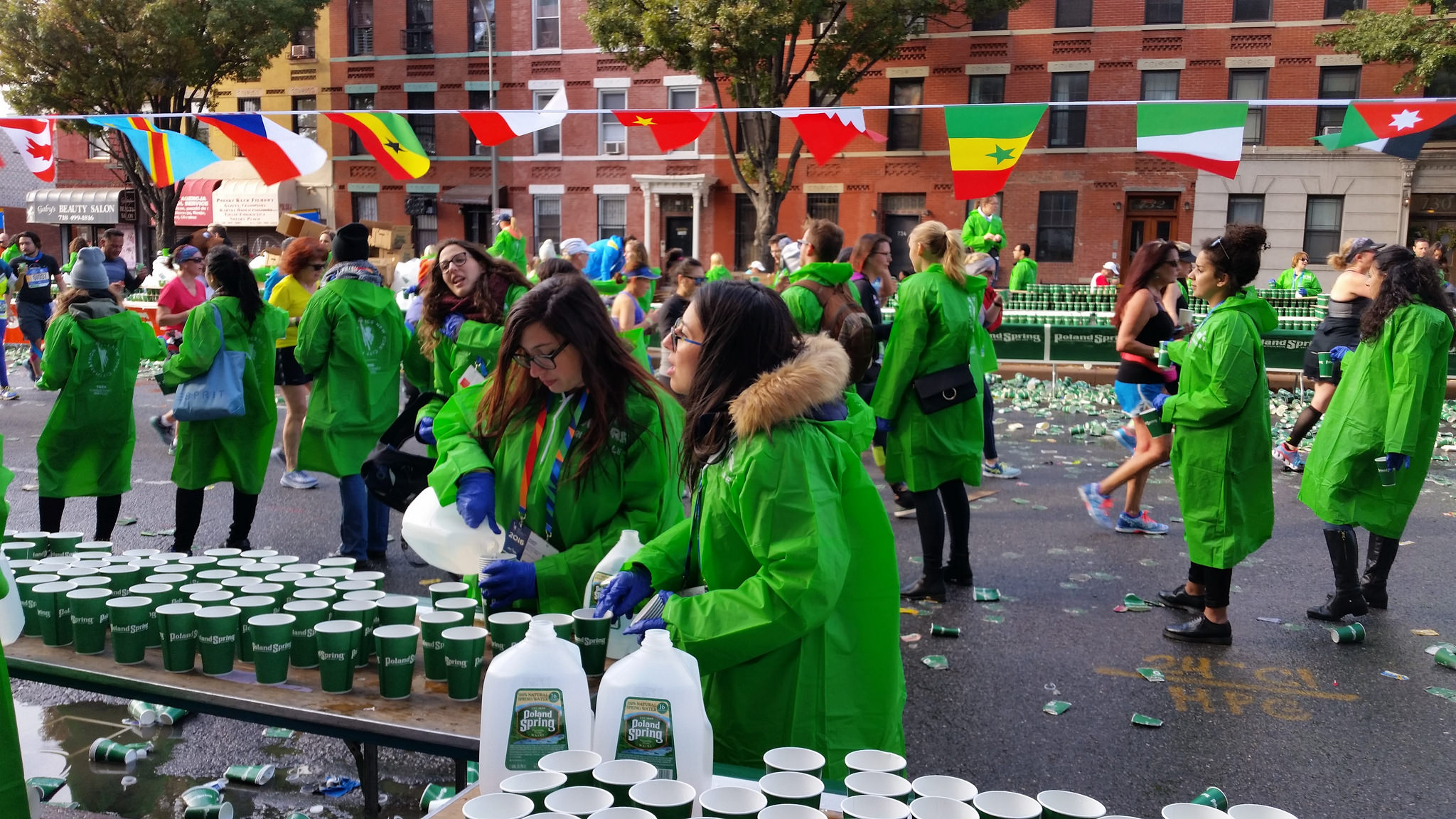 Two girls pour water from gallon jugs into paper cups for marathon runners