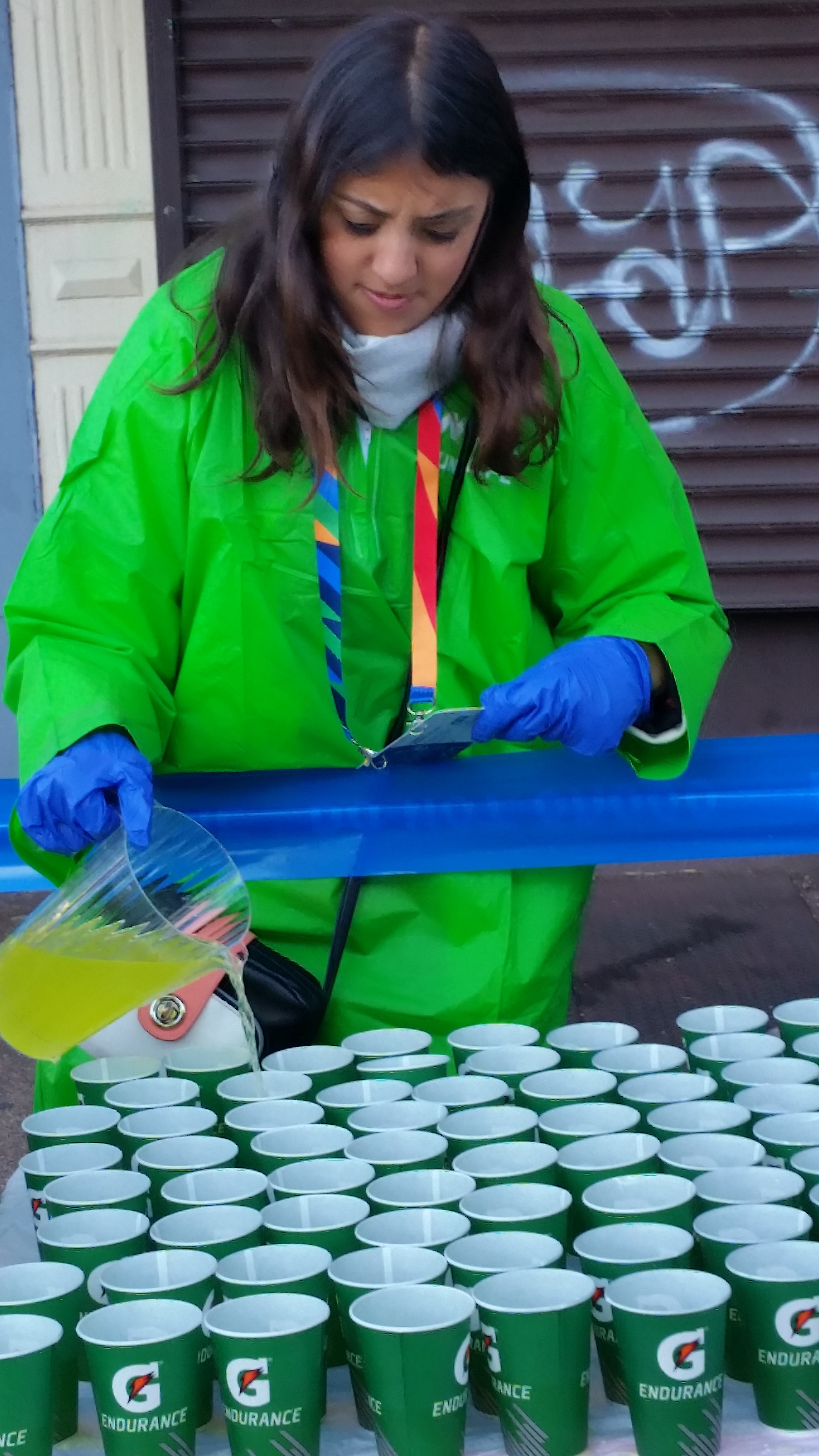 Young woman in green parka pouring yellow sports drink from pitcher into paper cups