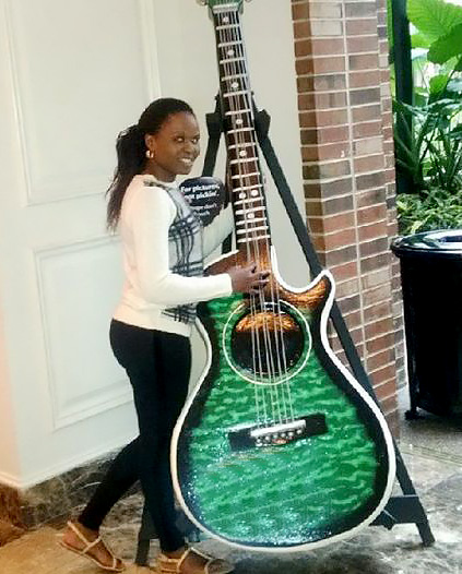 Faith poses with guitar on display at the Country Music Hall of Fame and Museum.