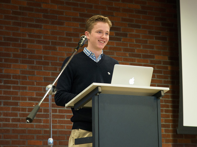Young white man standing behind a podium with an Apple MacBook giving a presentation