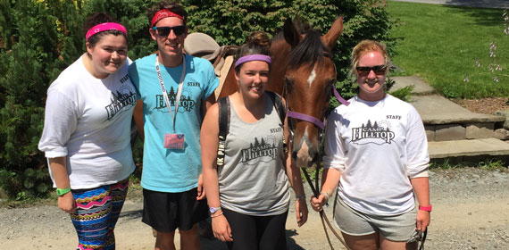 camp counselors pose together with a horse