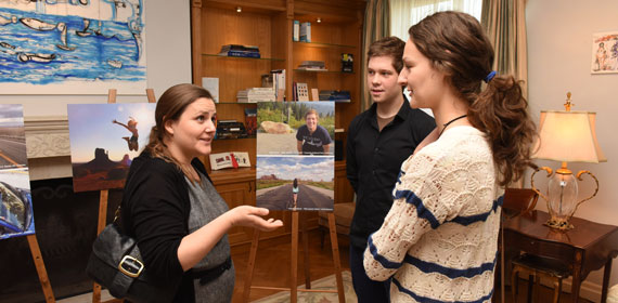 J-1 alumni and prospective participants having conversation in front of a photo display