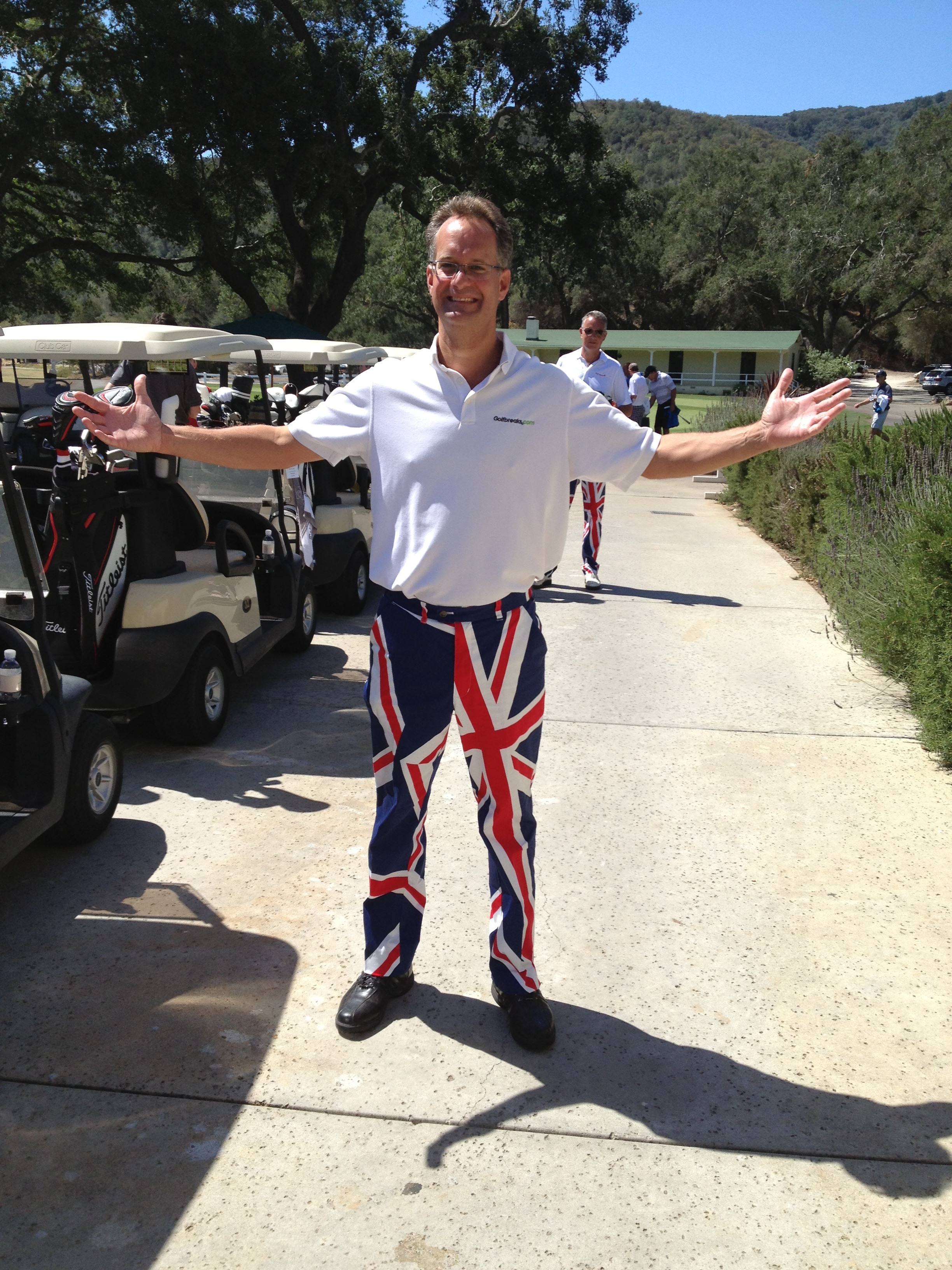 Man standing with arms stretched wide near golf carts