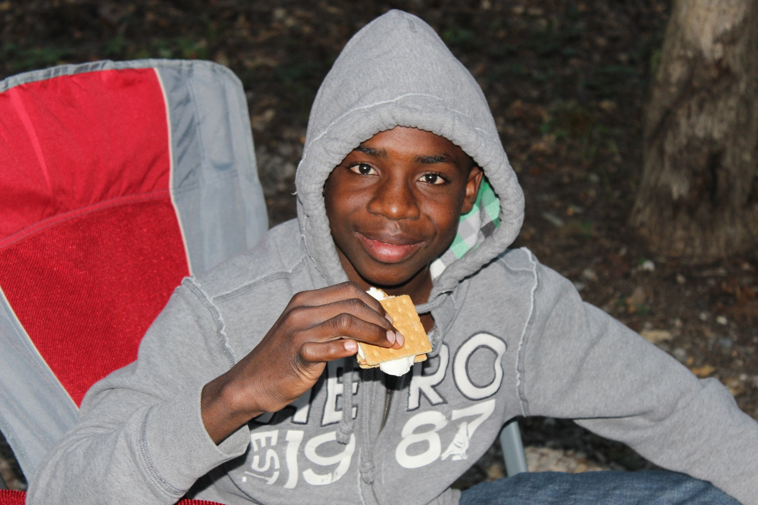 Young black boy smiling holding a s'more
