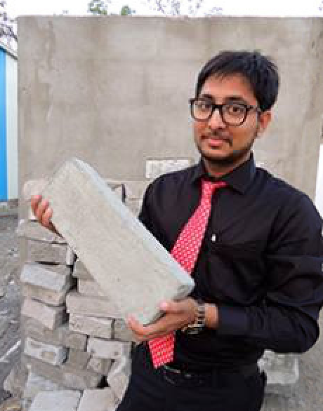 Binish Desai and the brick his company makes from industrial waste.