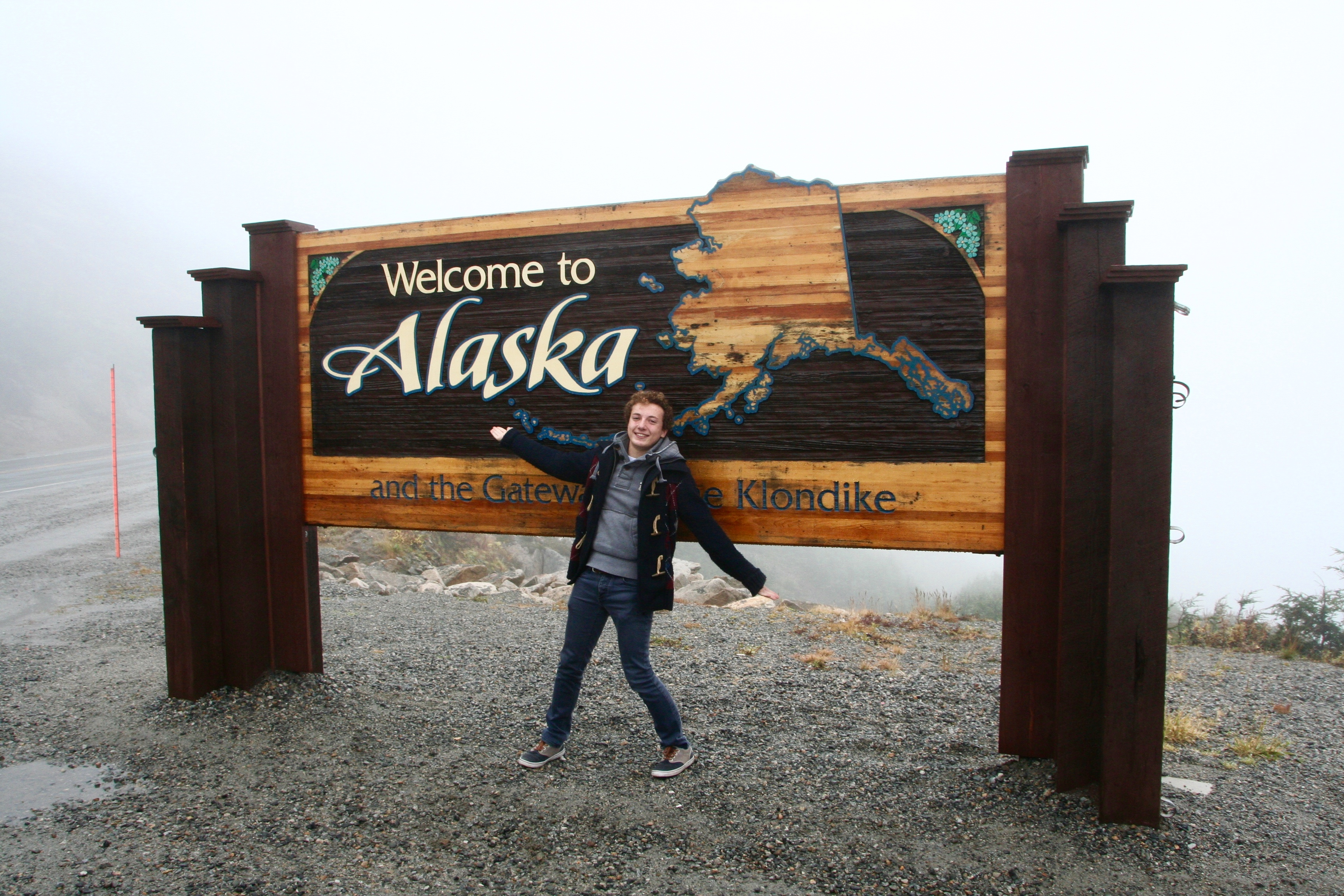 participant standing in front of sign saying Welcome to Alaska
