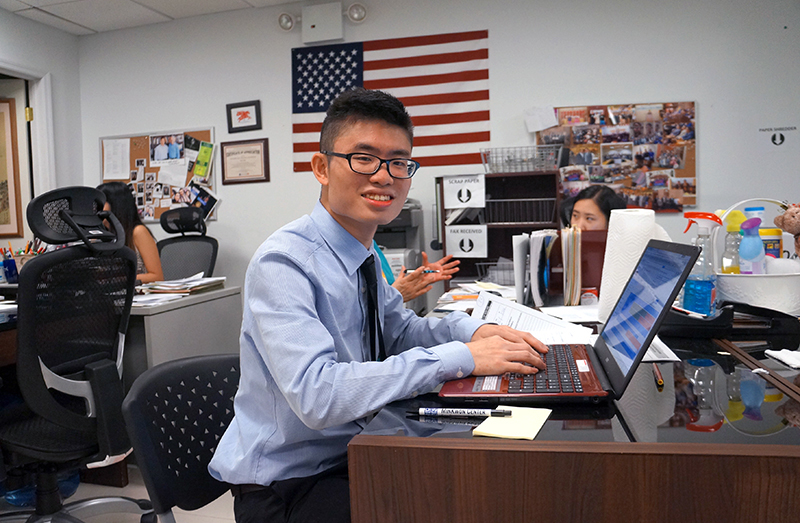tony chau at desk smiling
