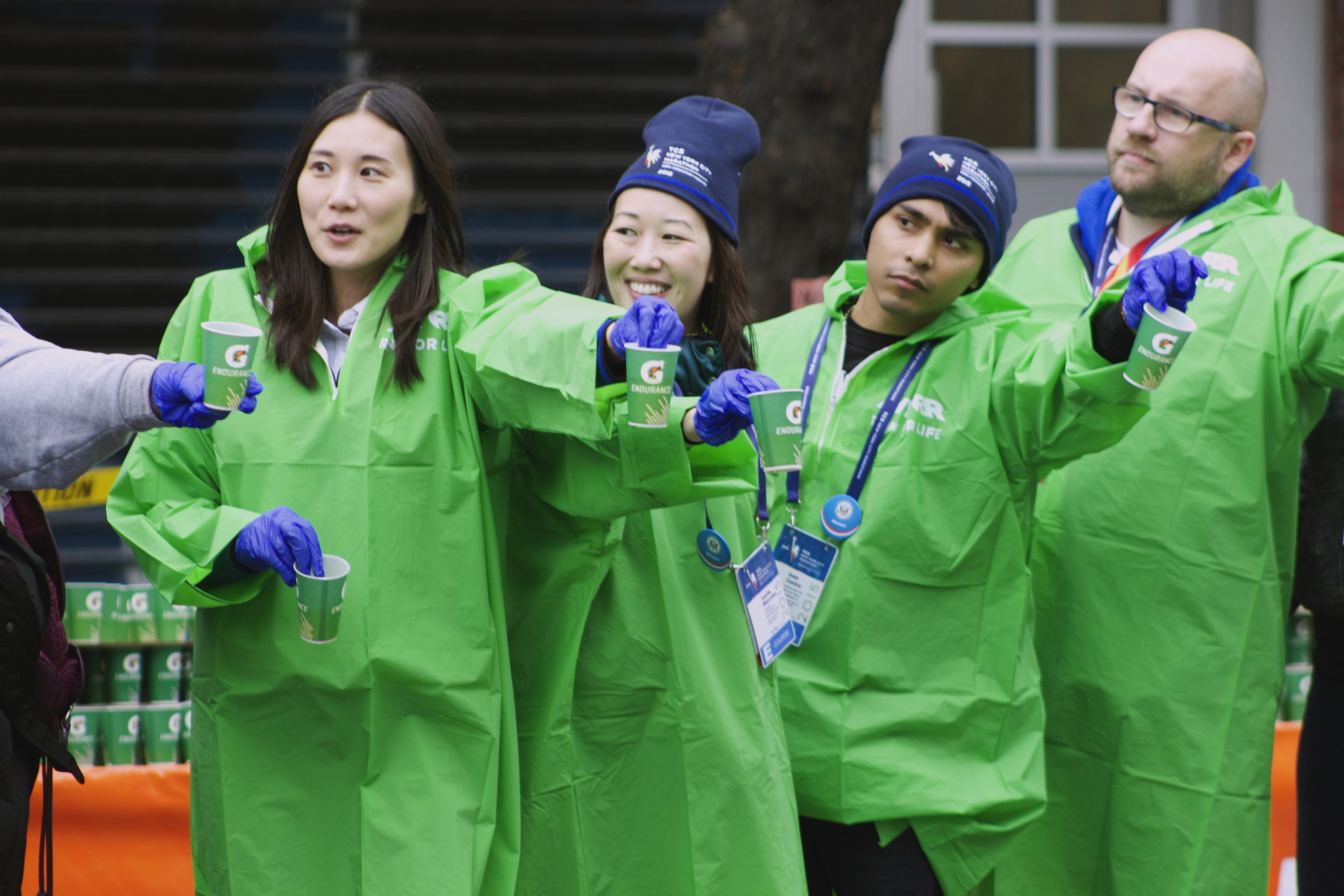 Four young people in green rain slickers hold cups of water on side of marathon course.