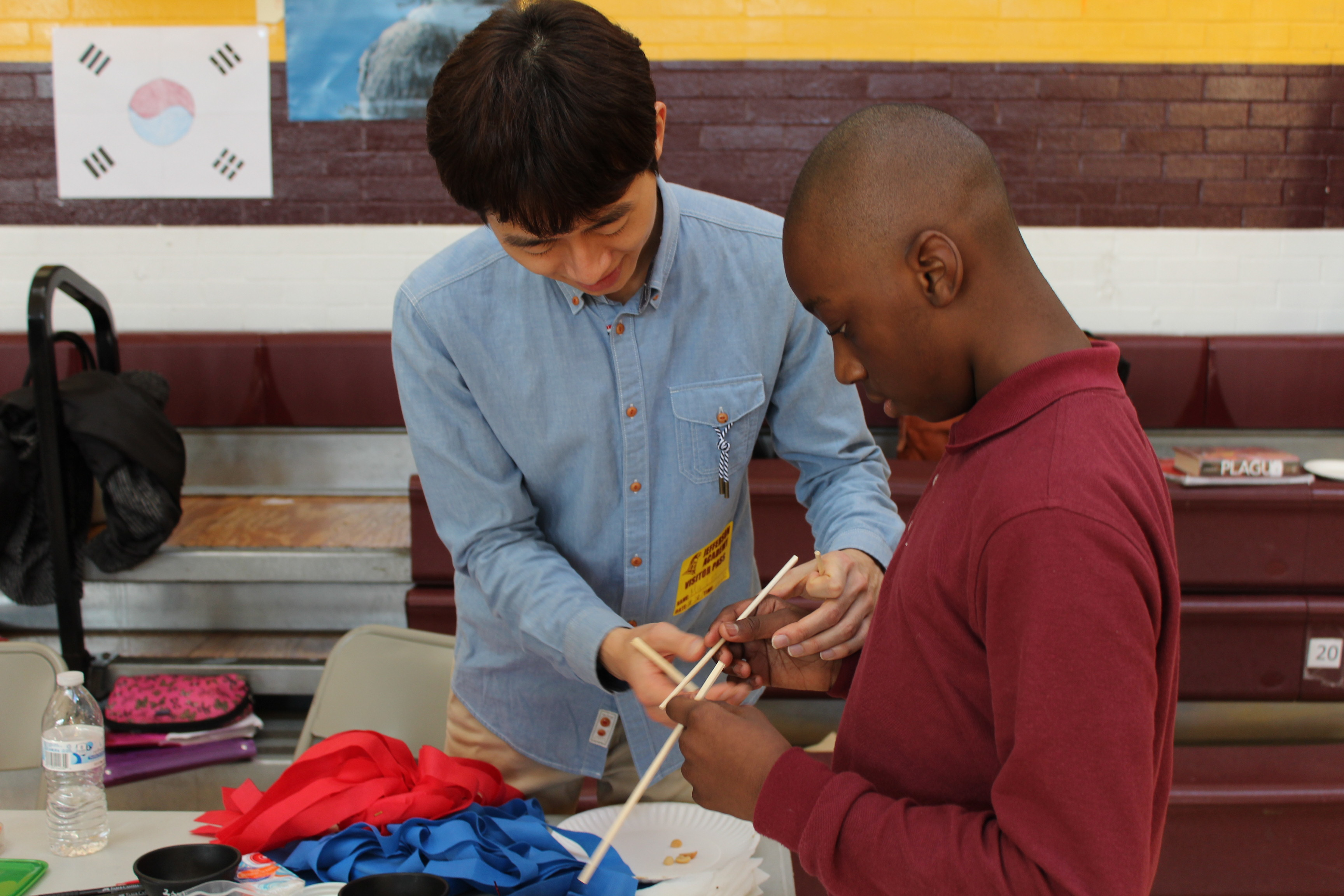 A Korea WEST exchange participant teaches an American student in Jefferson High School in D.C. how to use chopsticks and a play Jegichagi (Korean hacky sack).