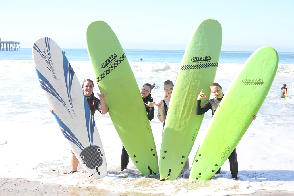 Four professional au pairs with surfboards (left to right): Marina Da, Julia Hinderhofer, Saskia Derkow (all from Germany), and Eva Spielbichler (from Austria), professional au pairs with APEX PROaupair