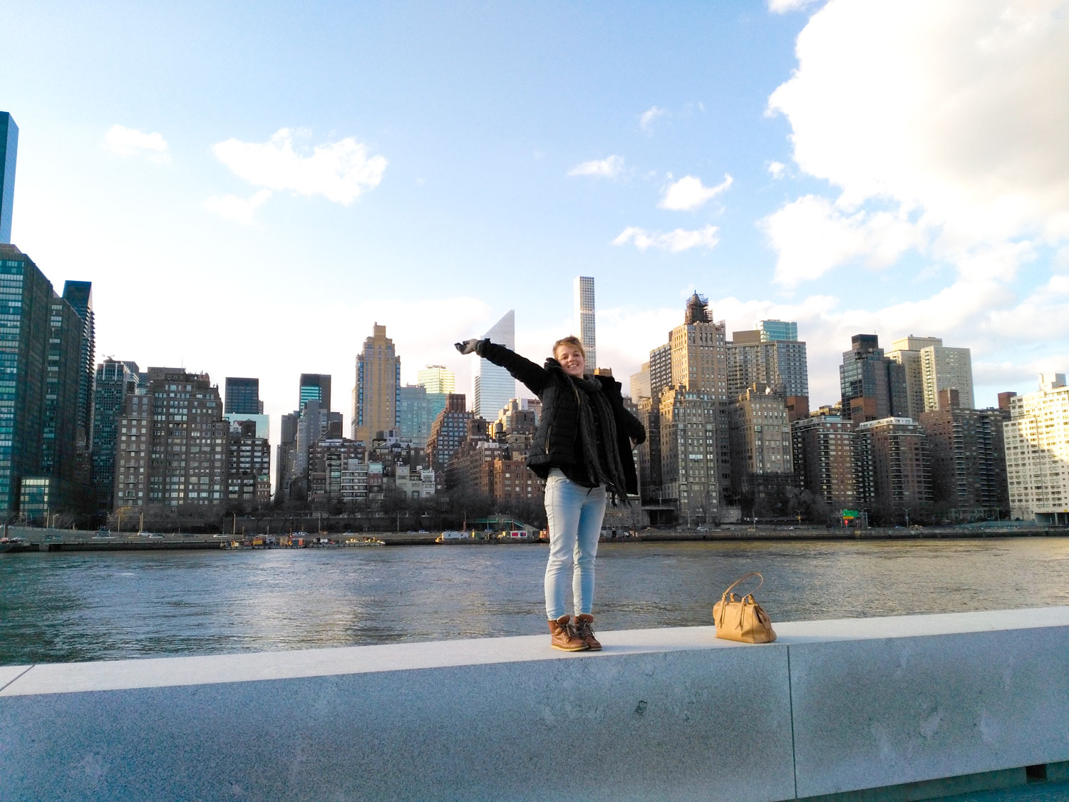 Stephanie poses with New York City Skyline from Roosevelt Island.