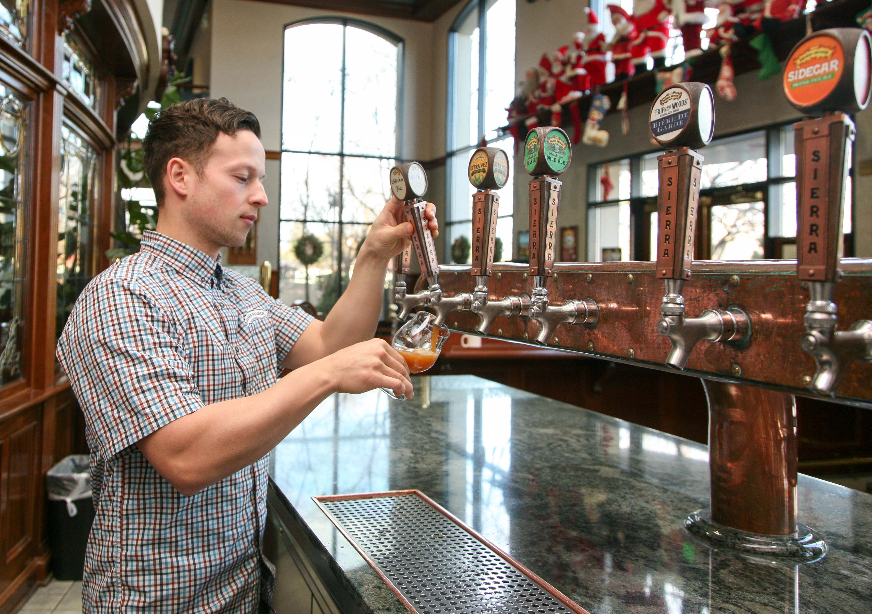 Young man pouring a beer from one of several taps behind a bar