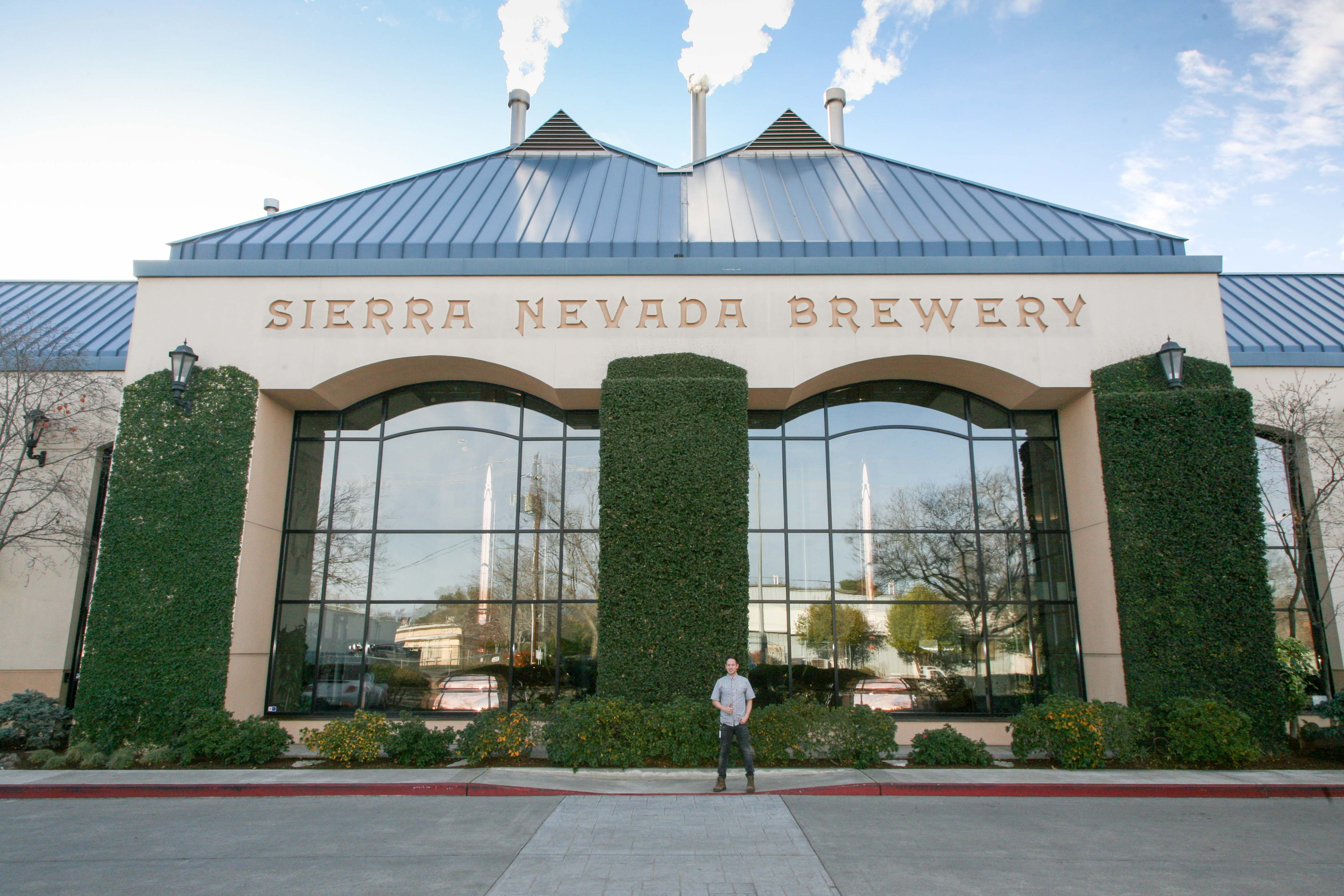 Young man standing in front of the Sierra Nevada Brewery
