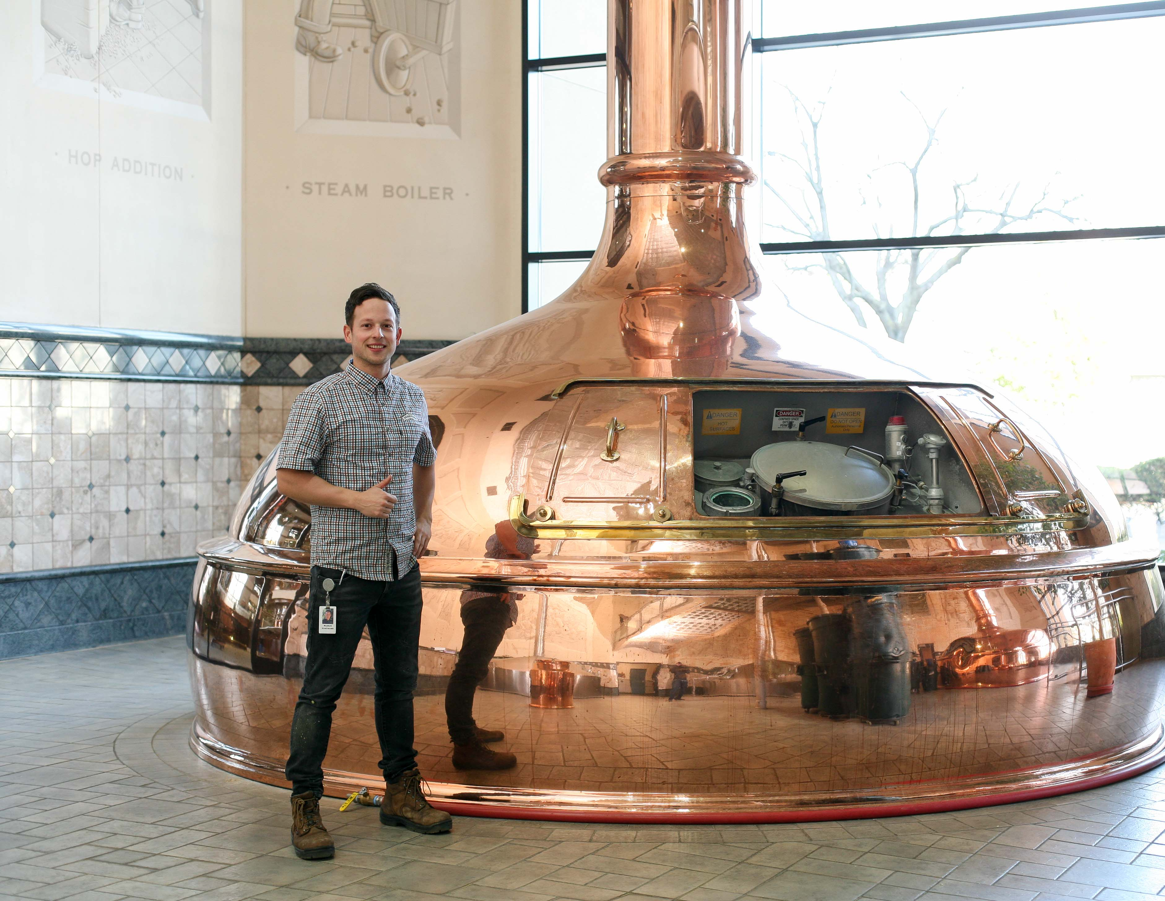 Young man in plaid shirt standing in front of a large brewing tank
